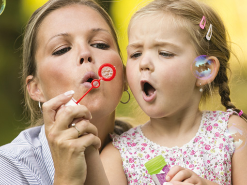 Image of mother blowing bubbles with young daughter