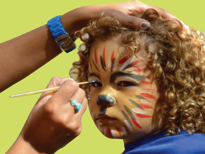 Picture of young boy having face paint applied at a party