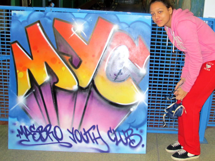 Picture of Masbro Youth Club girl with spray can stood by her artwork interpretation of Masbro Youth Club logo