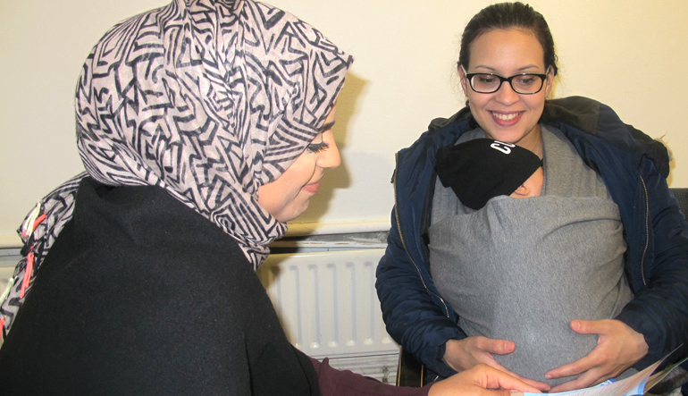 Picture of young mum talking a Masbro outreach worker sure start