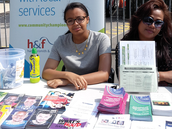Picture of female volunteers at a stall promoting Community Champions