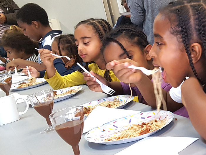 Picture of children eating a vegan meal laid on by Addison Community Champions