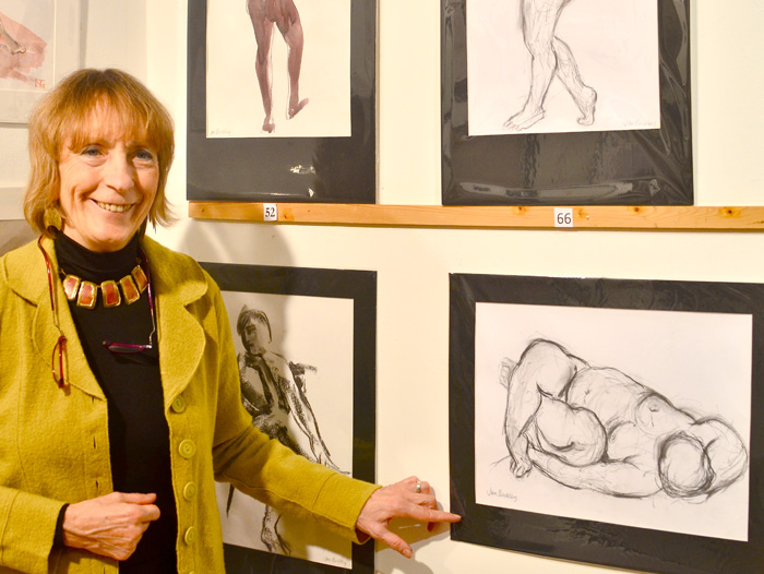 Woman standing next to her framed life drawing in an exhibition at