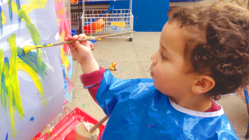 Image of boy painting at Masbro Children's Centre